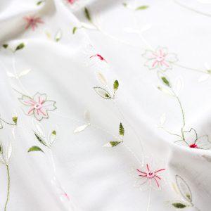 dettaglio del tessuto per tendine a vetro con fiorellini ricamati e colorati su fondo bianco